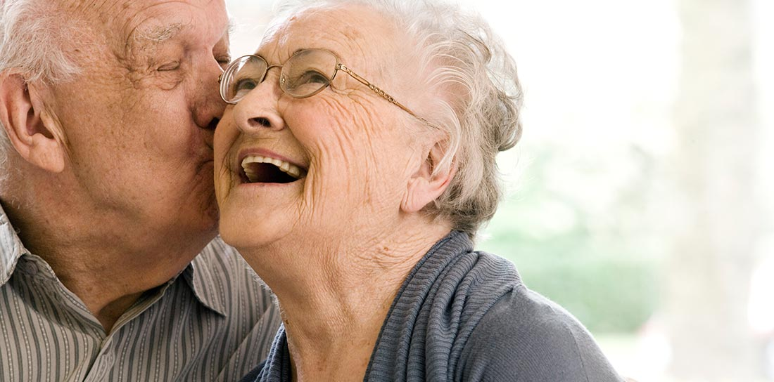 senior man kisses his wife on the cheek
