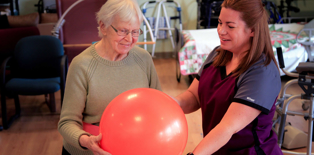 physical therapist helps senior woman with a medicine ball