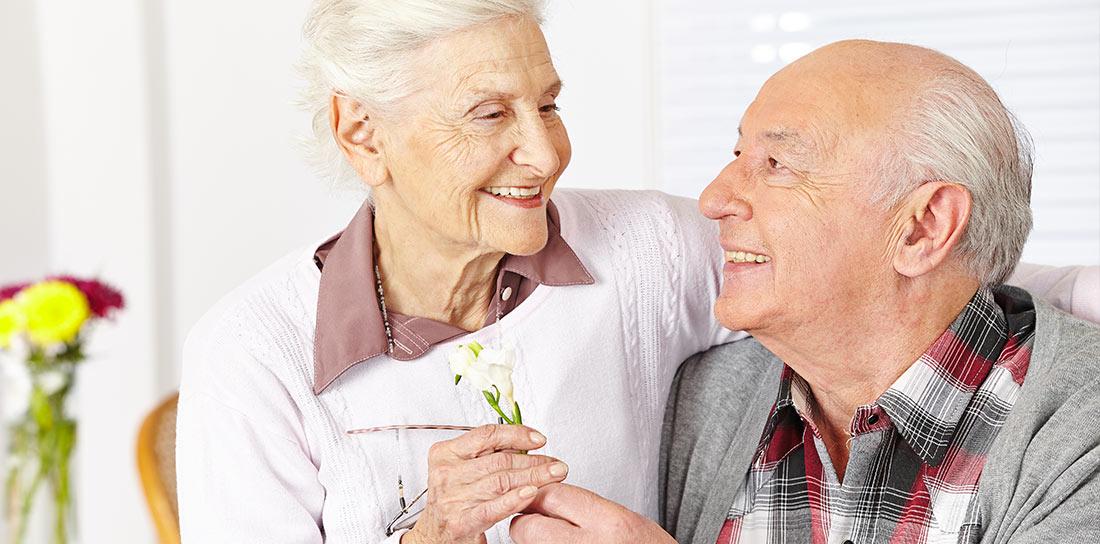 elder couple smile over a flower