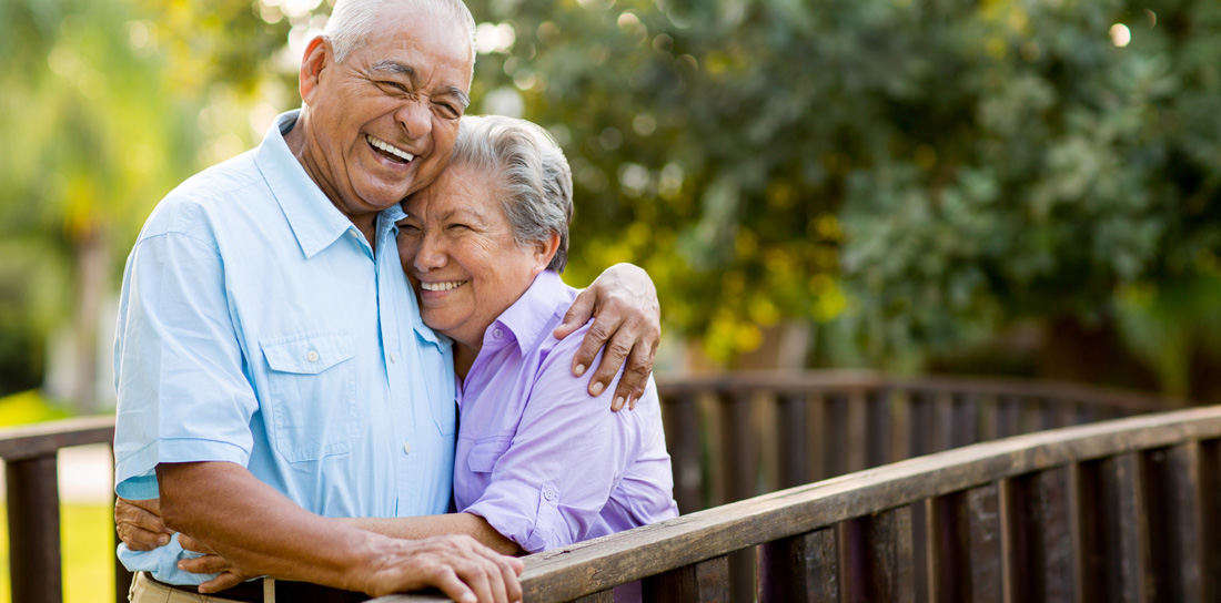 hispanic senior couple embracing and laughing