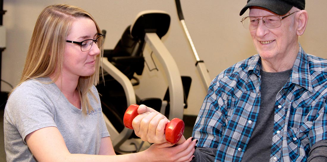 physical therapist works with senior man