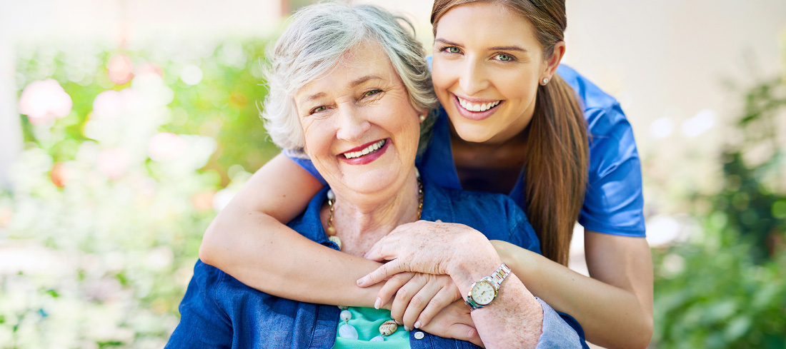 smiling young woman embraces older woman