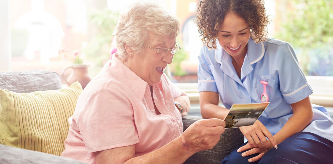 nurse reads a postcard with her elderly patient