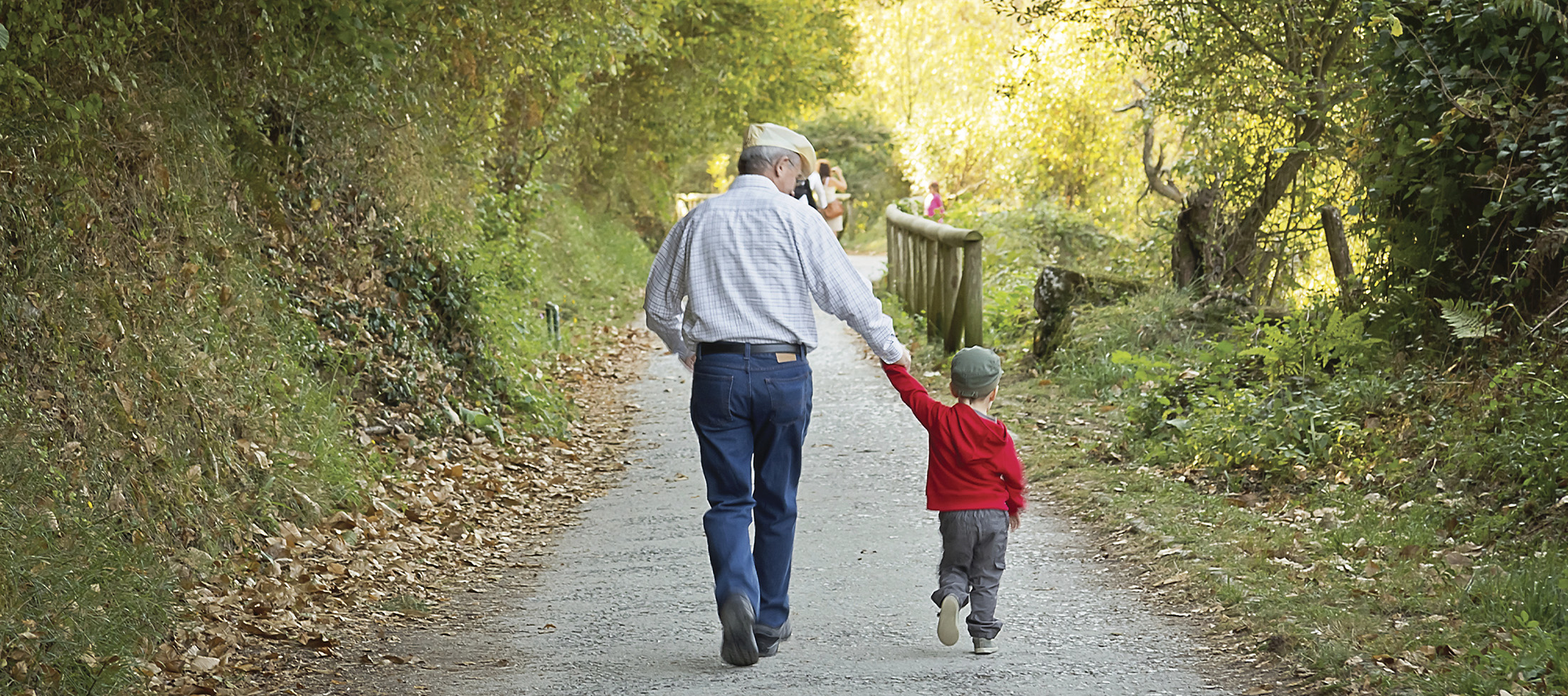 grandpa holds grandson's hand on a walk