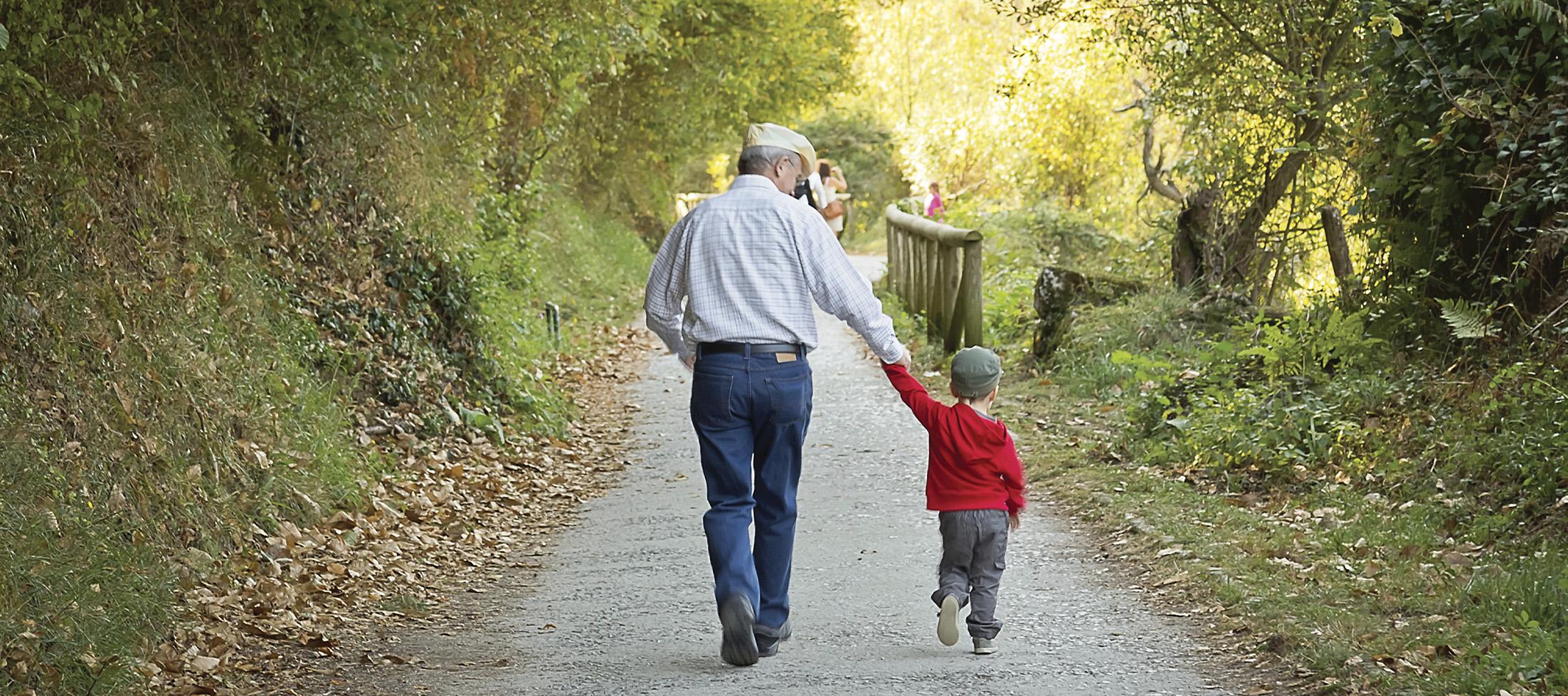 grandpa holds grandson's hand on a walk